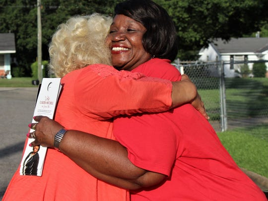 Claudia Mitchell, a candidate facing Robert Porterfield Jr. in a runoff election for the District 6 Board of Education Democratic nomination, hugs her childhood friend, Regina Craig Avery, while canvassing the Mobile Heights neighborhood on Tuesday, June 19.