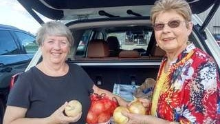 Columbia Civitan President Carlene Messick and Civitan member Emily Marshall showing Vidalia onions.