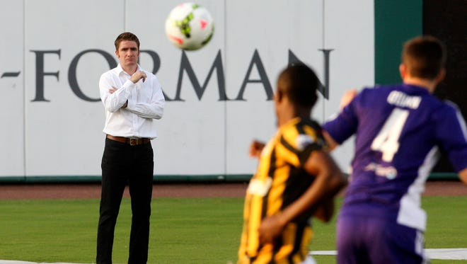 Louisville City FC coach James O'Connor watches the play on the pitch from the sidelines.   