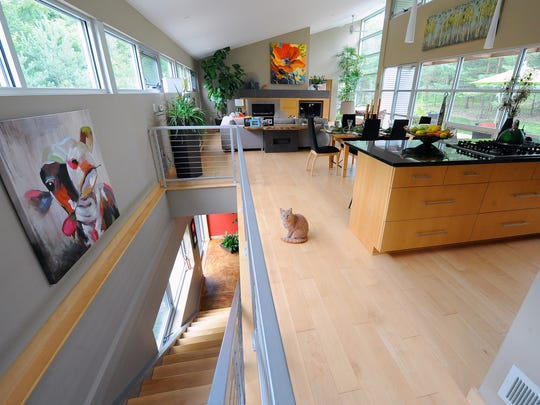 The main floor features open-concept living, dining and kitchen areas. Murphy the cat looks on cautiously.