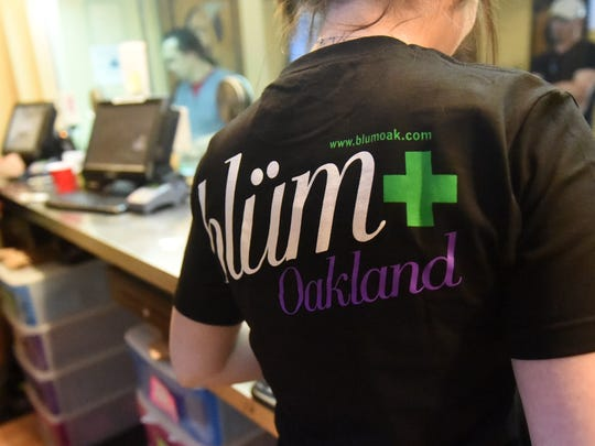 Staff work behind the counter selling medical marijuana to patients at Blum, a medical marijuana dispensary in Oakland, Calif.