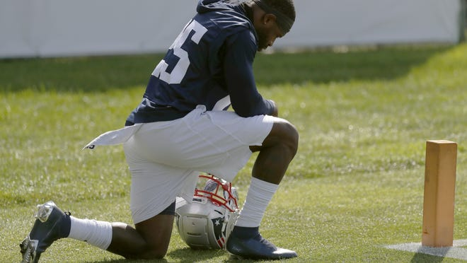 New England Patriots defensive back Terrence Brooks kneels briefly before walking onto the field for Friday's training camp practice in Foxborough.