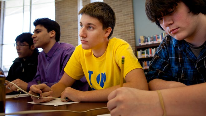 Students Robbie Bacheller, 16, and Travis Sparks, 17, write out their work for a math problem as they scrimmage with teachers in preparation for the state Quiz Bowl tournament.