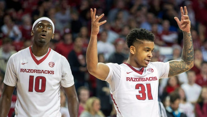 Arkansas guard Anton Beard, right, celebrates after a defensive stop alongside forward Bobby Portis, left, during the first half of an NCAA college basketball game against South Carolina on Tuesday, Feb. 3, 2015, in Fayetteville, Ark.