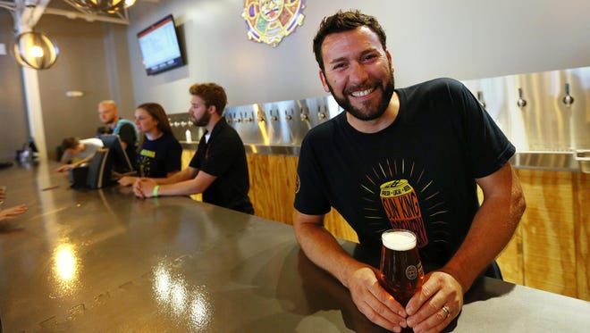 Clay Robinson, a co-owner of Sun King Brewery, stands behind the bar at the new Sun King tap room in Fishers.