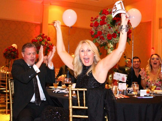 Rob Forsythe applauds as his wife Kim Forsythe has the winning bid for a trip to Scotland.