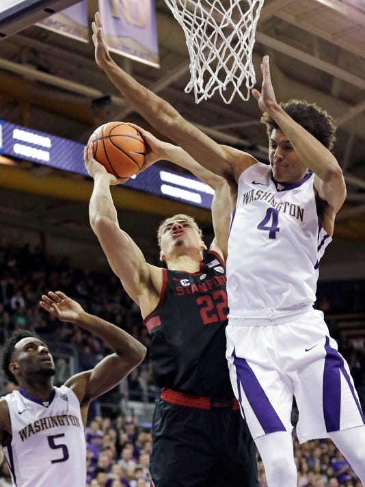 Stanford's Reid Travis (22) shoots between Washington's Matisse Thybulle (4) and Jaylen Nowell (5) in the first half of an NCAA college basketball game Saturday, Jan. 13, 2018, in Seattle. (AP Photo/Elaine Thompson)