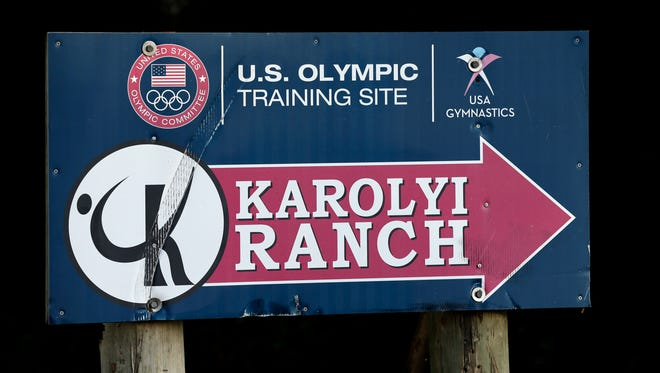 In this Sept, 12, 2015 photo, a sign points down the road to the Karolyi Ranch near New Waverly, Texas. Texas Gov. Greg Abbott on Tuesday, Jan. 30, 2018, has ordered a criminal investigation into claims that former doctor Larry Nassar abused some of his victims at the Texas ranch that was the training ground for U.S. women's gymnastics.