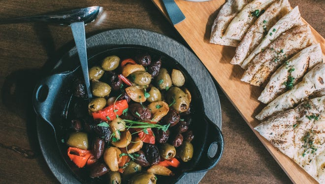 Wood-fired Qcom olives and grilled flatbread from Tres Tempe, a Southwestern-Mediterranean fusion restaurant in Tempe.