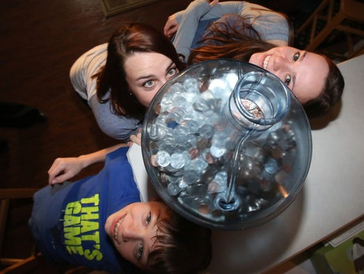 Kevin, 12, Julianne, 19 and Allison Rogers, 17, with a bottle filled with change their family has been collecting for several years at their Nanuet home March 11, 2014.