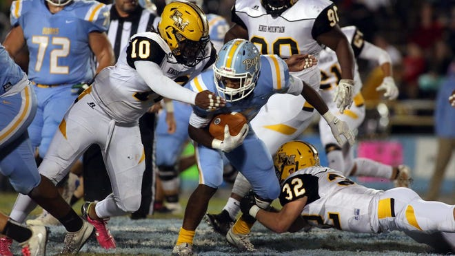 Burns Kujuan Pryor carries the ball as Kings Mountain Dameon Wilson and Nathan Groves move in to stop the play during their game at Burns High School on Friday.