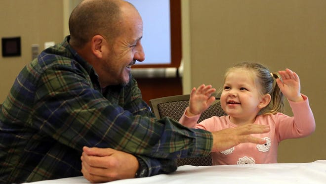 Wayne Gates has fun with daughter Allison, 2, at a celebration for her adoption held at the LeGrand Center.