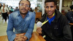 In this Nov. 20, 2018 photo, Ethiopian paralympic athletes Megersa Bati, left, and Tamiru Kefeyalew Demisse, holding the silver medal he won in the 1,500 meters race at the 2016 Paralympics, pose for a photo in Sao Paulo, Brazil. (AP Photo/Andre Penner)
