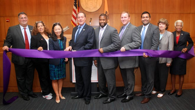 Acting Union County Prosecutor Grace H. Park cuts the ribbon for the Union County Family Justice Center with eight members of the Union County Board of Chosen Freeholders (L-R, Alexander Mirabella, Linda Carter, Prosecutor Park, Board Chairman Bruce H. Bergen, Mohamed S. Jalloh, Christopher Hudak, Sergio Granados, Bette Jane Kowalski, and Vernell Wright).