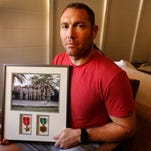 Robert D'Andrea, a retired Army major and Iraq war veteran, holds a frame with a photo of his team on his first deployment to Iraq on Friday at his home in Los Angeles. Nearly 10,000 California National Guard soldiers have been ordered to repay huge enlistment bonuses a decade after signing up to serve in Iraq and Afghanistan. The Pentagon demanded the money back after audits revealed overpayments by the California Guard under pressure to fill ranks and hit enlistment goals. If soldiers refuse, they could face interest charges, wage garnishments and tax liens,  D'Andrea said he was told to repay his $20,000 because auditors could not find a copy of the contract he says he signed.