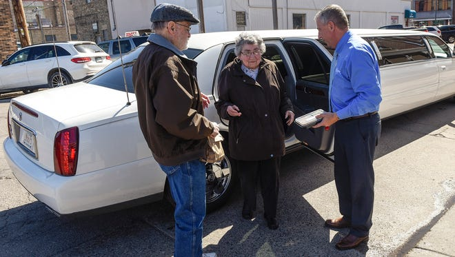 Emerging from a limousine, Bernie and Marge Kersting with St. Cloud Mayor Dave Kleis do their Home Delivered Meals route Thursday, April 19, around St. Cloud. The Kersting's were treated for their years of volunteering with the limousine to drive them.