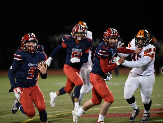 Marcus Martin (51) and Jack Yardley (62) lead the blocking for QB Jacob Kelbert as he scrambles for 55 yards against Flushing setting up the game-winning field goal during the regional final Nov. 10.