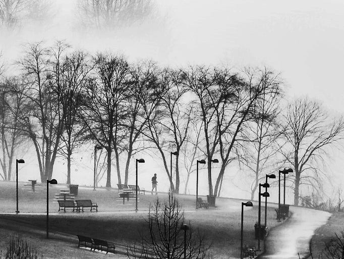 Waterfront Park is shrouded in fog and mist as a person