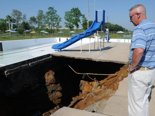 Iona Swim Club board President Todd Scipioni on Friday surveys the damage after an underground pipe burst, causing sinkholes that led to the collapse in the sidewalk between the baby pool and the main pool.