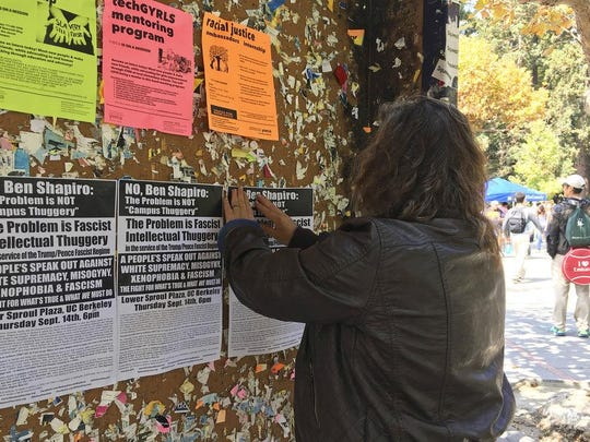 A woman tapes fliers Sept. 8, 2017 on a University of California, Berkeley campus bulletin board calling for a protest against right-wing speaker Ben Shapiro, who is set to speak there on Sept. 14.