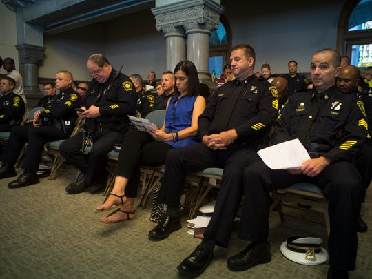 Cincinnati FOP president Dan Hils (far right) waits to speak to city council as other members of the police department sit in attendance.