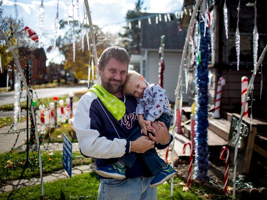 Derek Harper poses with his son Jon, 2, in front of his home at 520 S. Main St. in Marine City. Harper will begin the light show at his home and begin accepting letters to Santa Claus at 6 p.m. on Thanksgiving day.