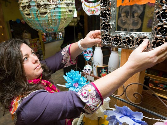 "A Hair & Body Shop/San Pasqual Market owner Kirstie Robles adjusts items in her shop on Saturday, October 28, 2017 during the Dia de los Muertos weekend. ""Day of the Dead is all year for me, I consider my store to be the Day of the Dead hotspot,"" said Robles, who has taken part in the local  festivities for 15 years. Robles is currently relocating her shop to 2222 Highway 28, but she says the festivities will continue,  ""Next year will be new, but it will be an equally amazing celebration. I love this weekend because it kicks off my favorite time of year."""