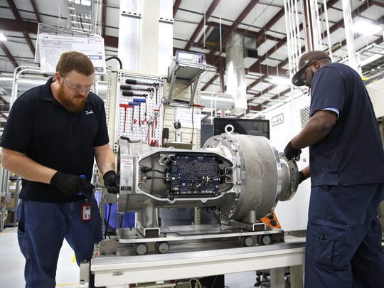 Production Technicians Chuck Flinkman, left, and Delvin Peoples work on assembling a compressor at the Danfoss Turbocor manufacturing facility Wednesday.