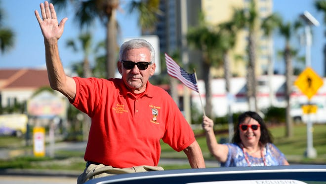 Cpl. Sonny Campbell waves to the crowd as Grand Marshall of the Pensacola Beach Veterans Day Parade on Wednesday.