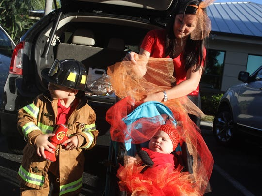 "MIchelle Horn helps get her 9 month old daughter Emma settled as son Ethan,4, stands nearby.  Emma was costumed as ""fire"" while Ethan was a fireman for the Trunks and Treats event held Saturday October 17 at the Milestones Learning Center in Estero. Parents and children decorated the trunks of their cars and then went trick and treating from car to car."