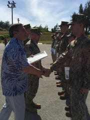 Gov. Eddie Calvo on Wednesday morning shakes Zackary Odom's hand before presenting him a certificate of appreciation for volunteering to help the Guam Vet Center on Veterans Day this past November. Odom is a member of the Naval Mobile Construction Battalion, or Seabees, who conduct construction projects on military installations.