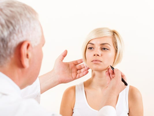 doctor plastic surgeon with patient examine woman, draw on face
