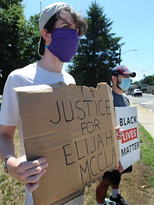 "Connor Donovan, 24, left, of Ashland, holds a ""Justice for Elijah McClain"" sign Thursday in Ashland's Montenegro Square. He and friends have been holding Black Lives Matter signs in downtown Ashland for the past three weeks, five days a week. McClain died last Aug. 24 after Aurora, Colorado, police placed him in a chokehold. Colorado Gov. Jared Polis has appointed a special prosecutor to review the case. Aurora police have since banned the chokehold used on McClain."