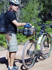 Walt Pheney checks his equipment during a break in the 215-mile bike ride over the moutains.