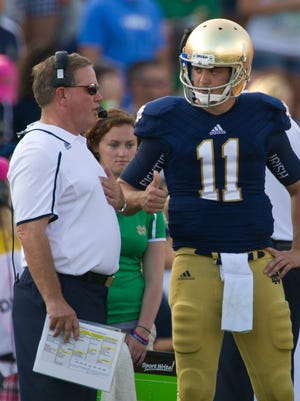 Notre Dame Fighting Irish quarterback Tommy Rees (11) talks with head coach Brian Kelly in the third quarter against the Temple Owls at Notre Dame Stadium.