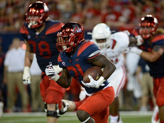 Arizona Wildcats running back J.J. Taylor (21) runs the ball against the Houston Cougars during the first half at Arizona Stadium.