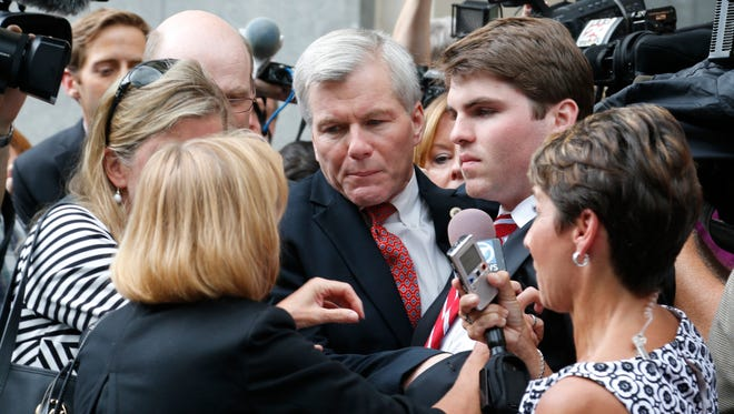 Former Virginia Gov. Bob McDonnell, center, is mobbed by media as he gets into a car with his son, Bobby, right,  after he and his wife, former first lady Maureen McDonnell, were convicted on multiple counts of corruption at Federal Court in Richmond, Va., Thursday, Sept. 4, 2014. A federal jury in Richmond convicted McDonnell on 11 of the 13 counts he faced; Maureen McDonnell was convicted on nine of the 13 counts she had faced. Sentencing was scheduled for Jan. 6.  (AP Photo/Steve Helber)