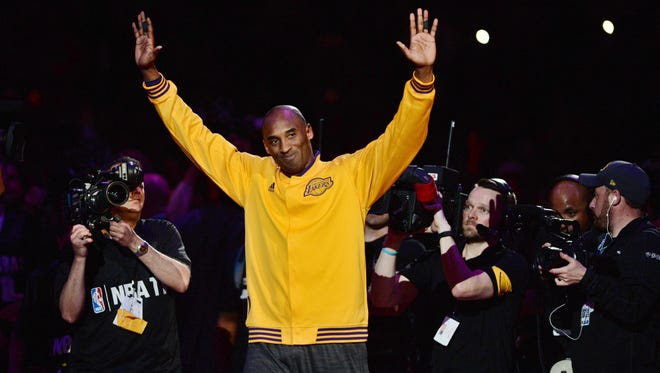 Kobe Bryant waves to the crowd as he walks on the court before his final game against the Utah Jazz at the Staples Center.