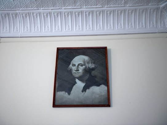A picture of George Washington hangs on the wall a