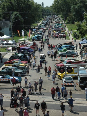 Crowds stroll past vehicles on display at the Gear-Head Get Together in Maple Lake.
