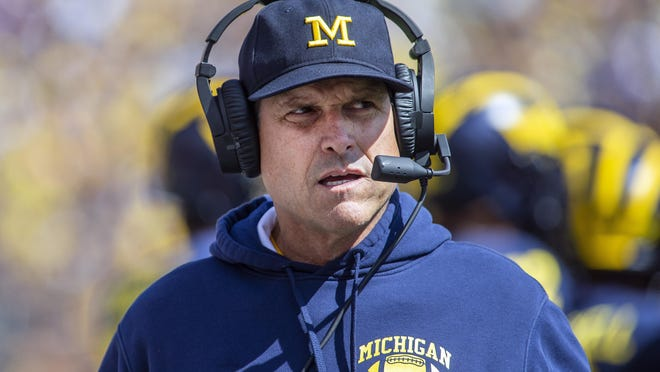 Michigan head coach Jim Harbaugh wears his headset on the sidelines in the first quarter of an NCAA football game against Army in Ann Arbor, Mich., Saturday, Sept. 7, 2019. Michigan won 24-21 in double-overtime.