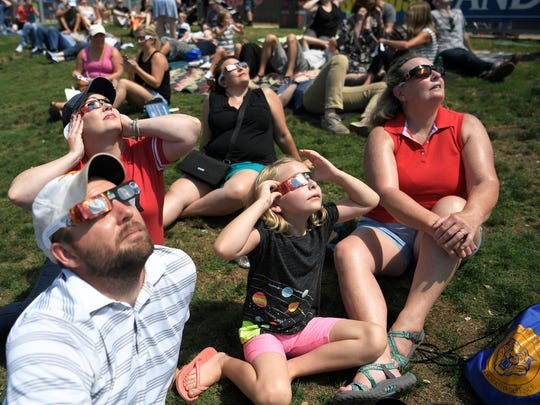 Spectators watch the eclipse at Nashville's eclipse-viewing party at First Tennessee Park Monday, Aug. 21, 2017 in Nashville, Tenn.