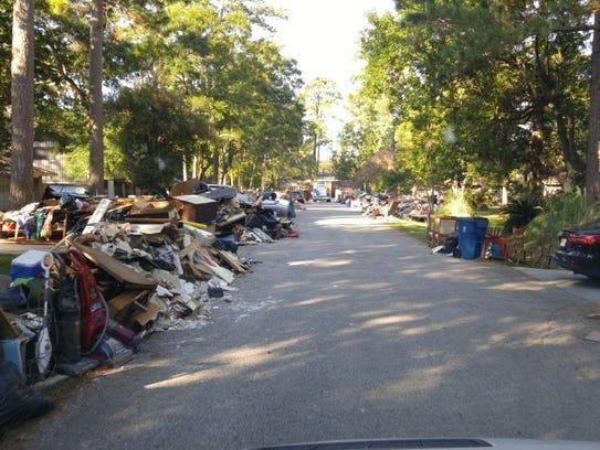 Flood-damaged and discarded items line a Texas street.