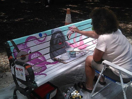 "Artist Nancy Gaddy works on her bench, titled ""Sing"
