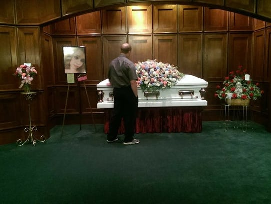 Chris Stansberry looks at the casket holding the body