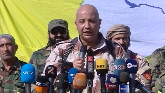 This frame grab from a video released Friday, Oct. 20, 2017 provided by Ronahi TV, a Kurdish TV channel media outlet, that is consistent with independent AP reporting, shows Talal Sillo, a spokesman and senior SDF commander speaks during a press conference held inside Raqqa city, Syria.