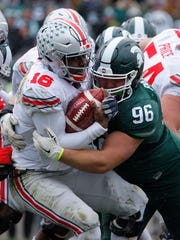 Ohio State quarterback J.T. Barrett, left, is sacked by Michigan State freshman Mike Panasiuk during Saturday's game.