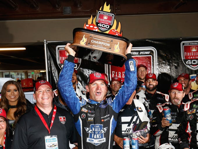 Clint Bowyer celebrates with the trophy after winning