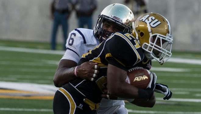 Alabama State University running back Robert Pritchett (#24) tries to escape during ASU's first home game of the season against Alcorn State University on Saturday, Sept. 12, 2015, in Montgomery, Ala.