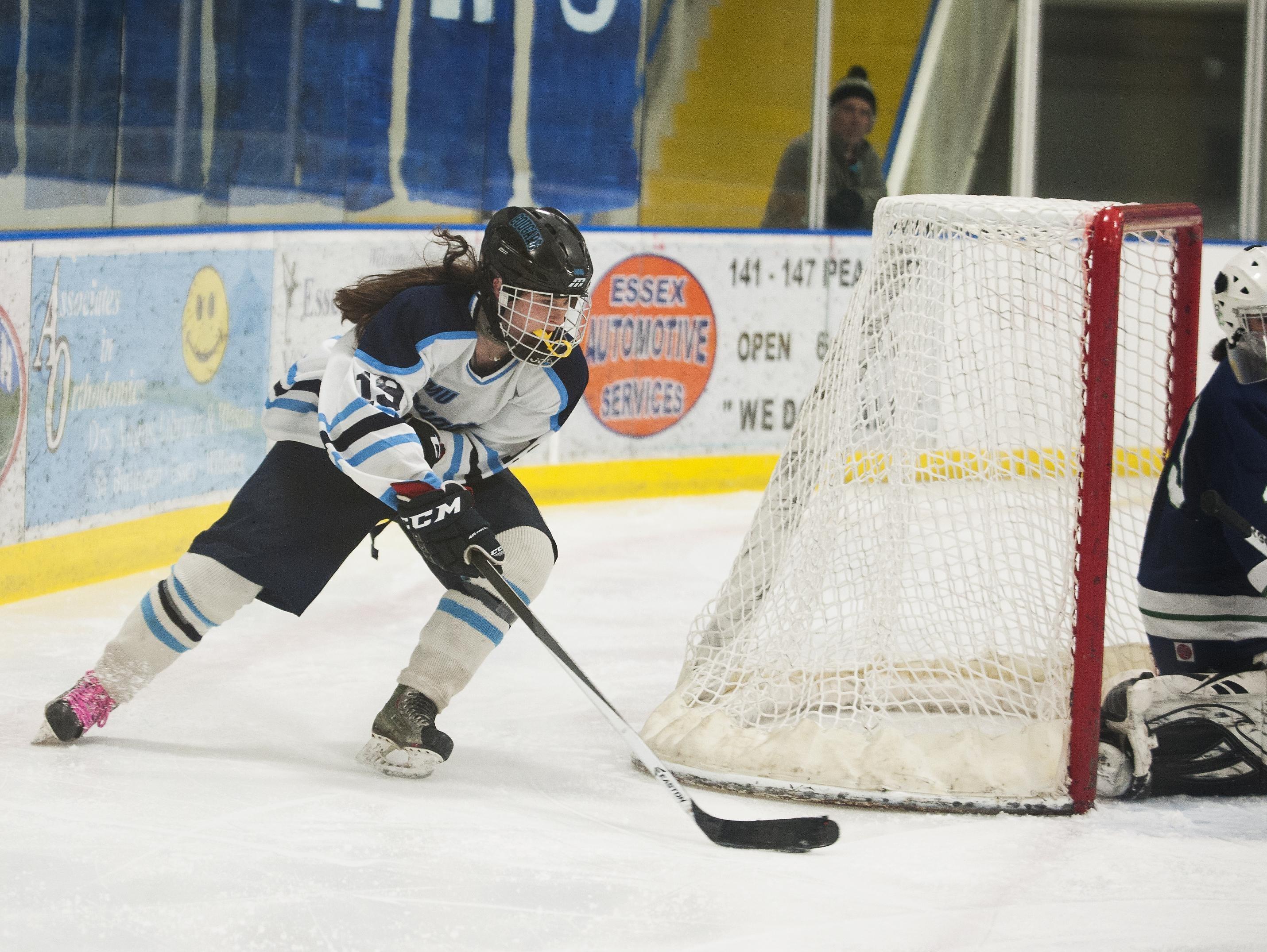 MMU's Anna Burke (19) skates around the net to take a shot during the girl playoff hockey game last season.